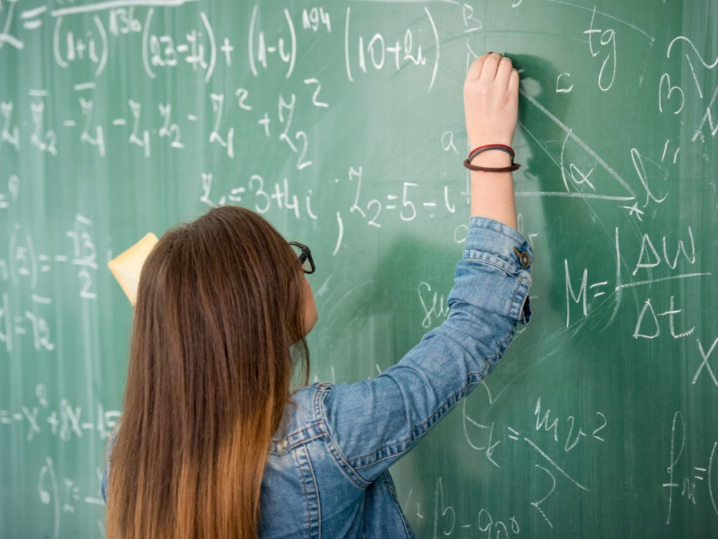 Schoolgirl with glasses writing on blackboard