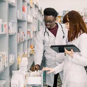 Portrait of two smiling friendly multiethnical pharmacists working in modern pharmacy and making order for medicines in distribution company