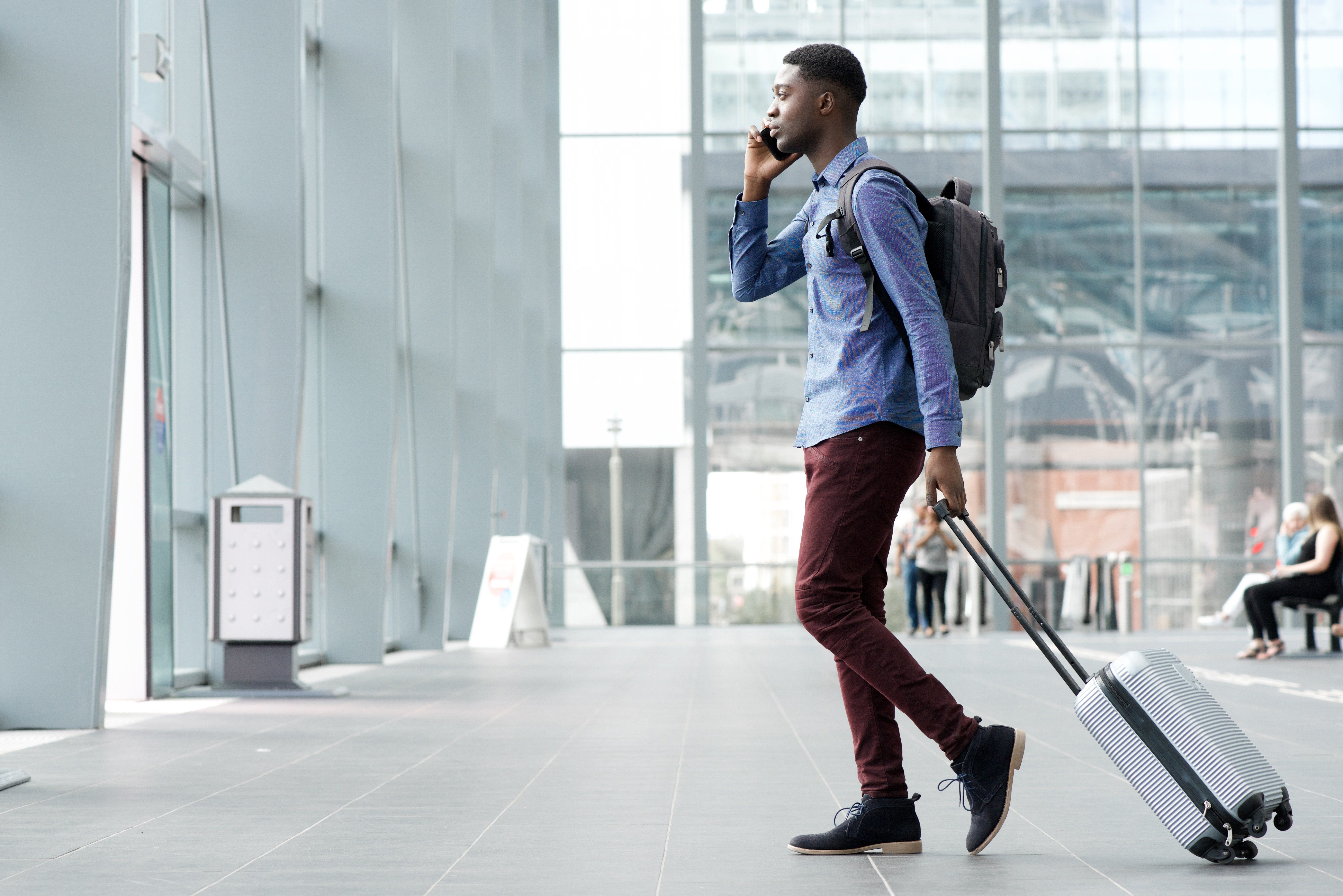 Full body side portrait of young african man traveling with suitcase and cellphone at airport