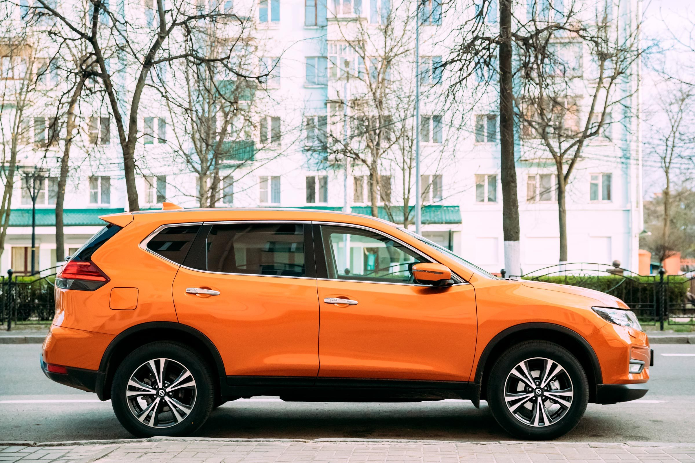 Orange Nissan X-Trail third generation Car Parked At Street. Side View