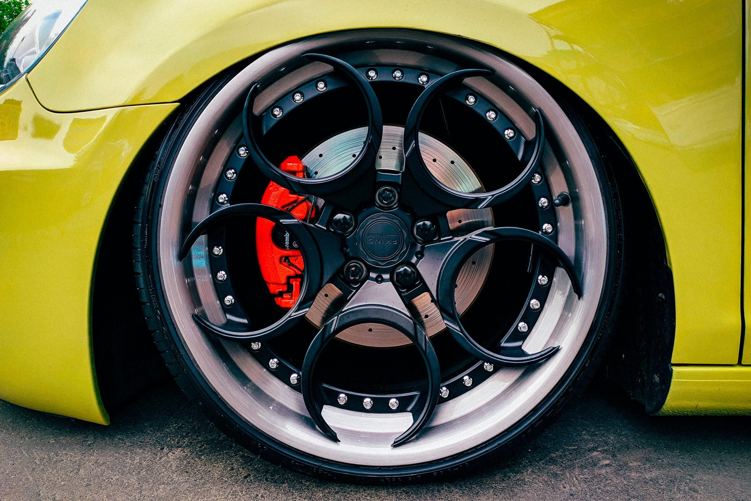 close up of custom wheels and brakes on a green car