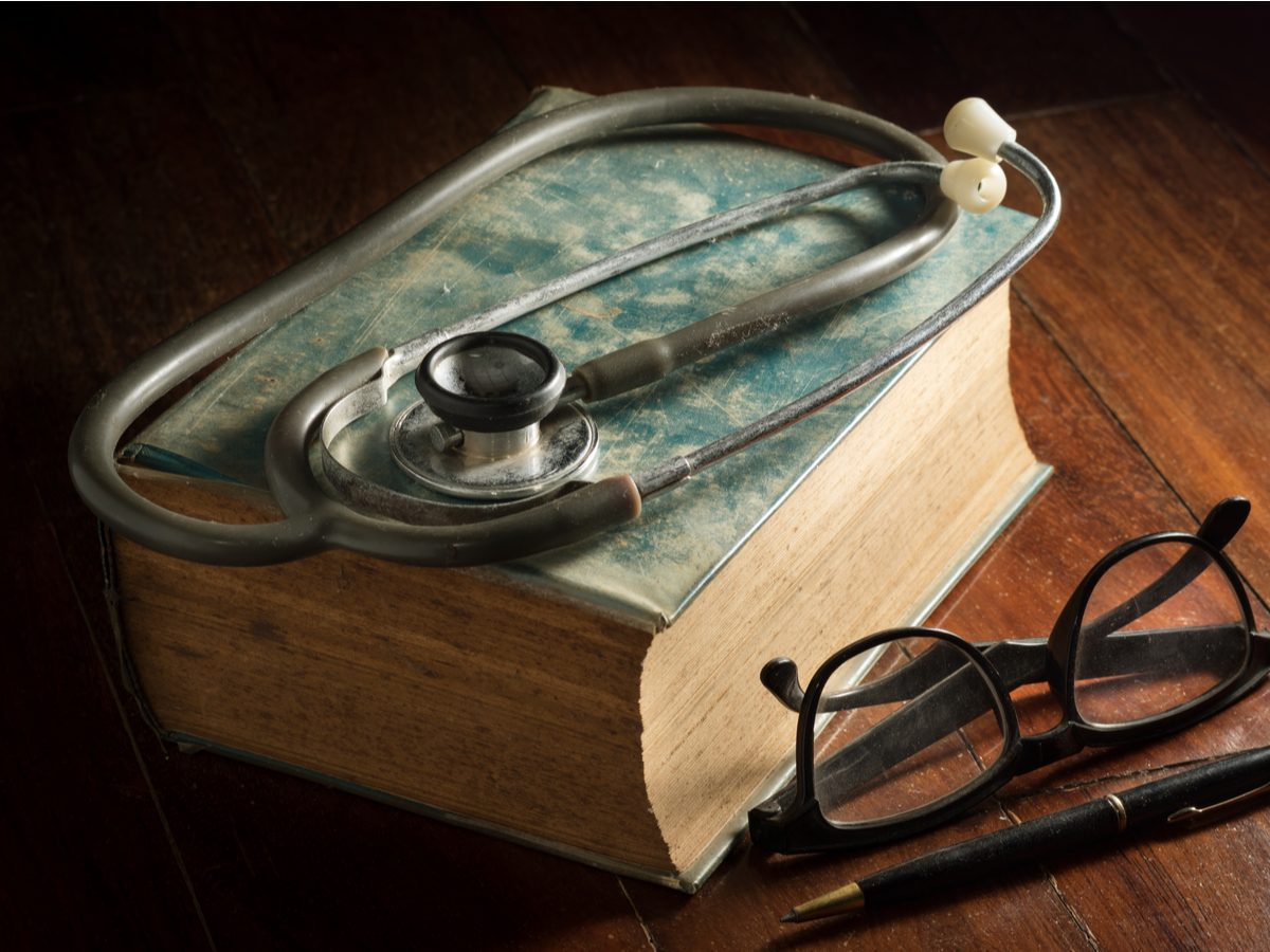 Stethoscope with eyeglasses, pen and antique book