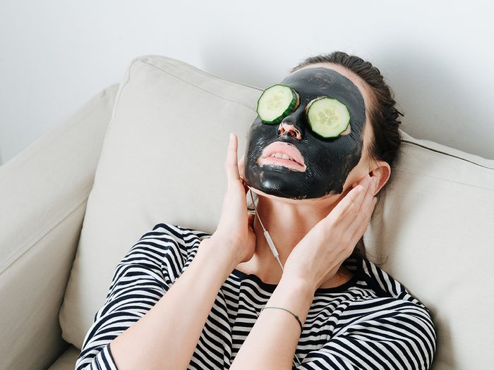 What does activated charcoal do - Young woman with bamboo charcoal peel off facial mask. Sitting in a couch at home, leaning her back. Hair in a bun. Cucumber slices over her eyes. Listening to the music.
