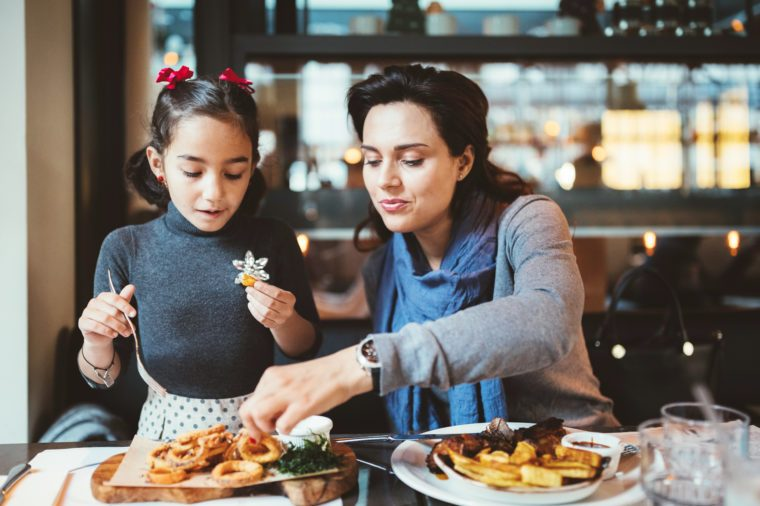 mother and daughter enjoying a meal in a restaurant