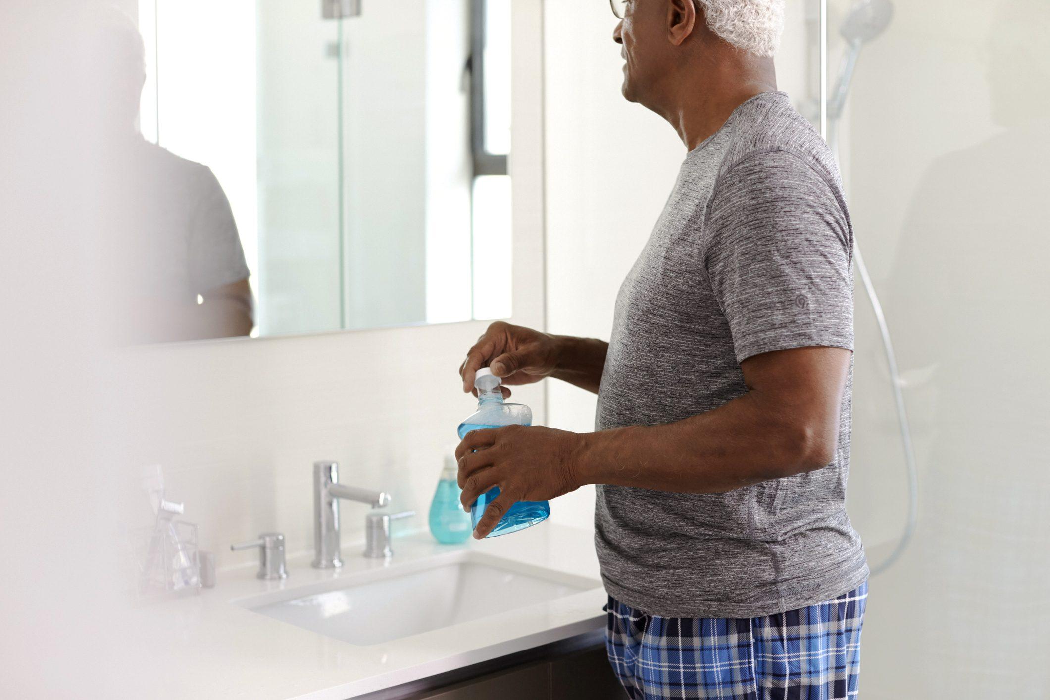 man using mouthwash in bathroom