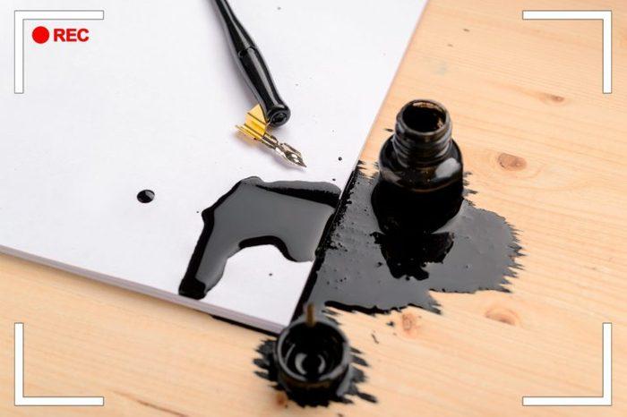 spilt black calligraphy ink on paper and desk.