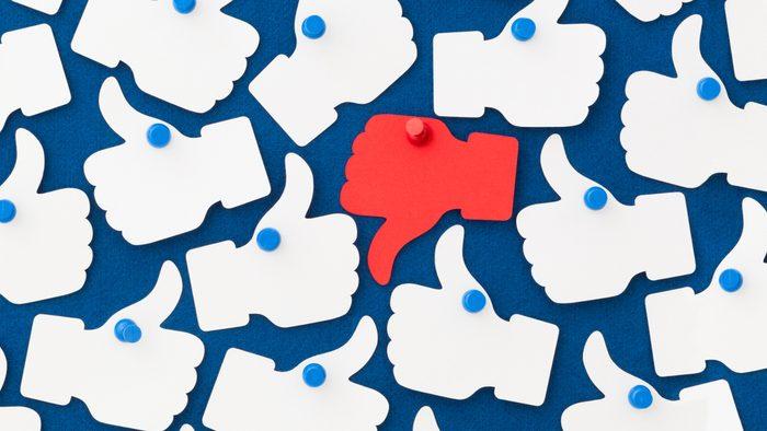 "facebook like and dislike concept. white ""like"" hands around one red ""dislike"" hand."