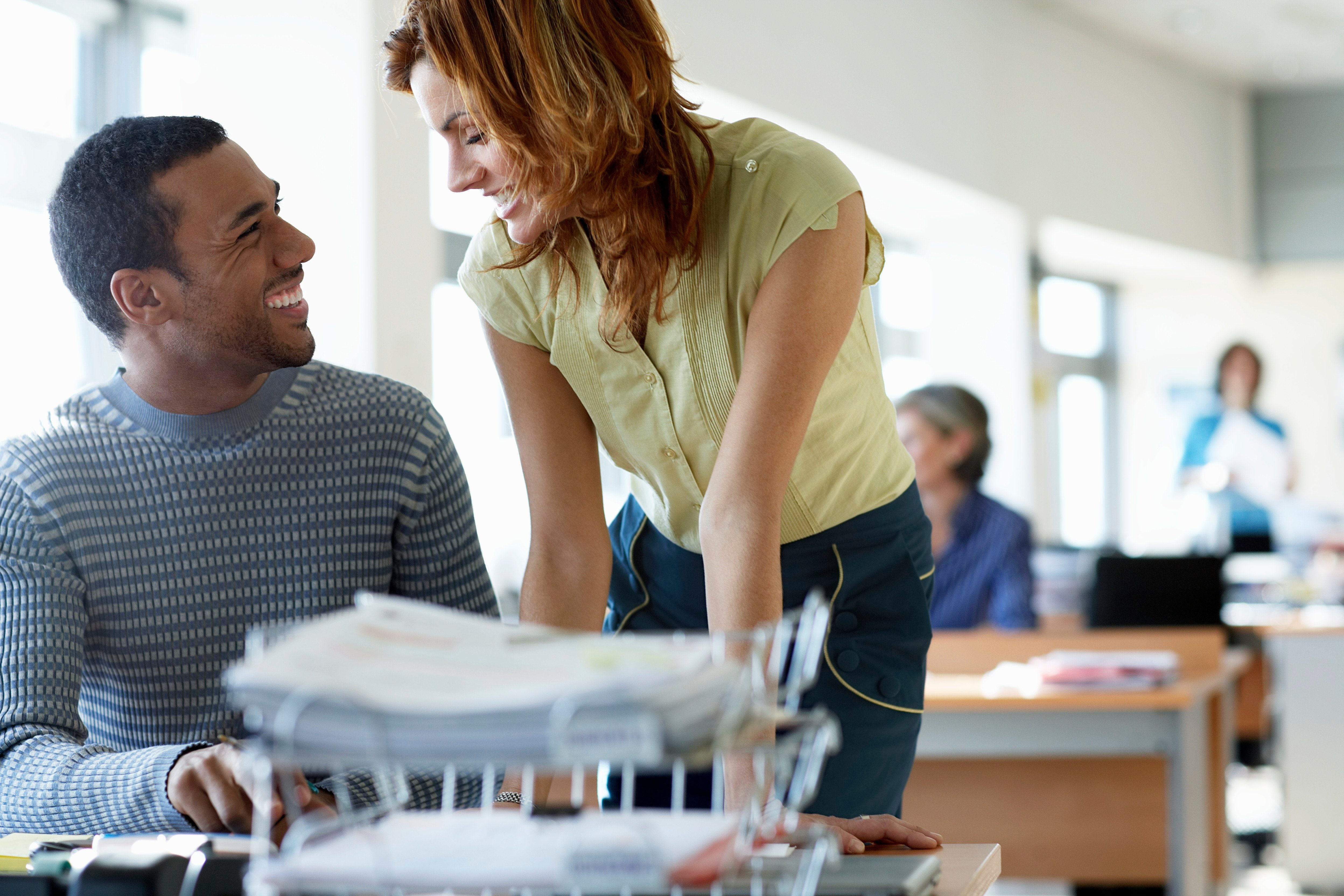 business man and business woman in an office. woman at the man's desk. smiling at each other.