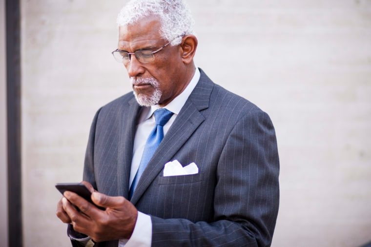 Portrait of an attractive senior business man using his phone
