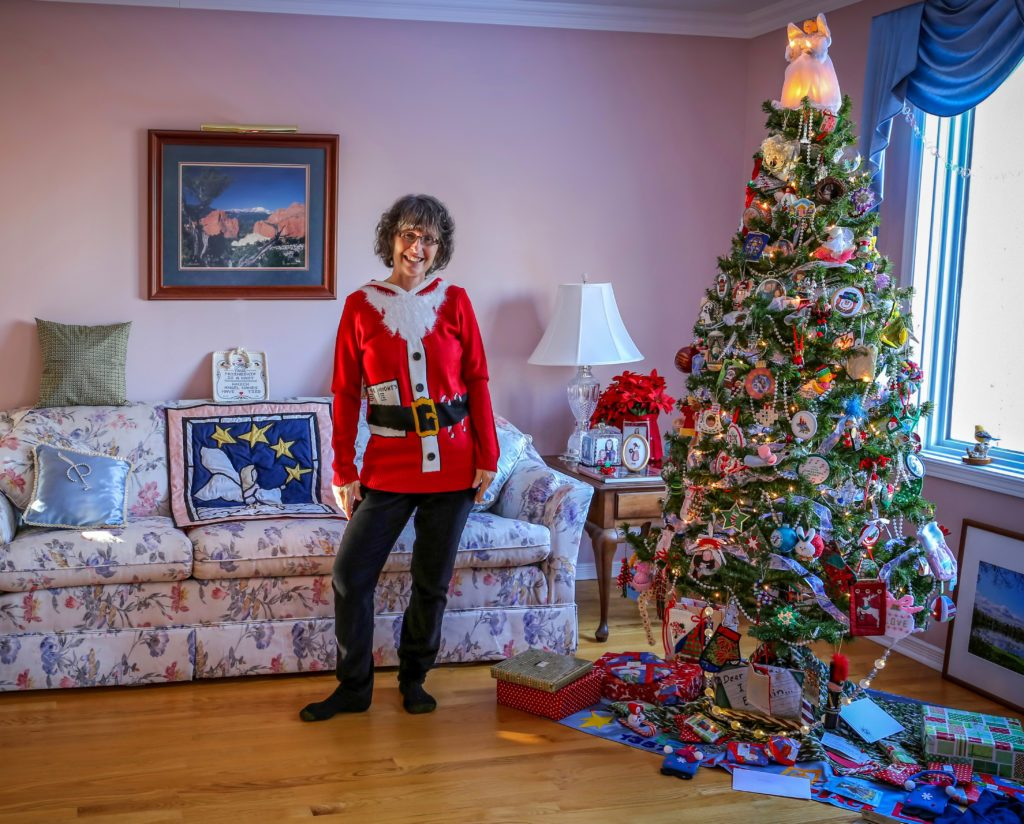 Woman in Santa sweater standing beside her Christmas tree