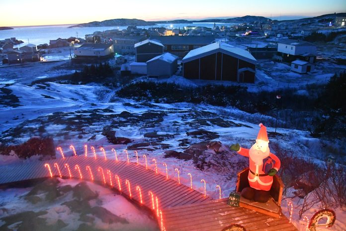 Plastic Santa figure looking out over the harbour in Cote Nord, Quebec