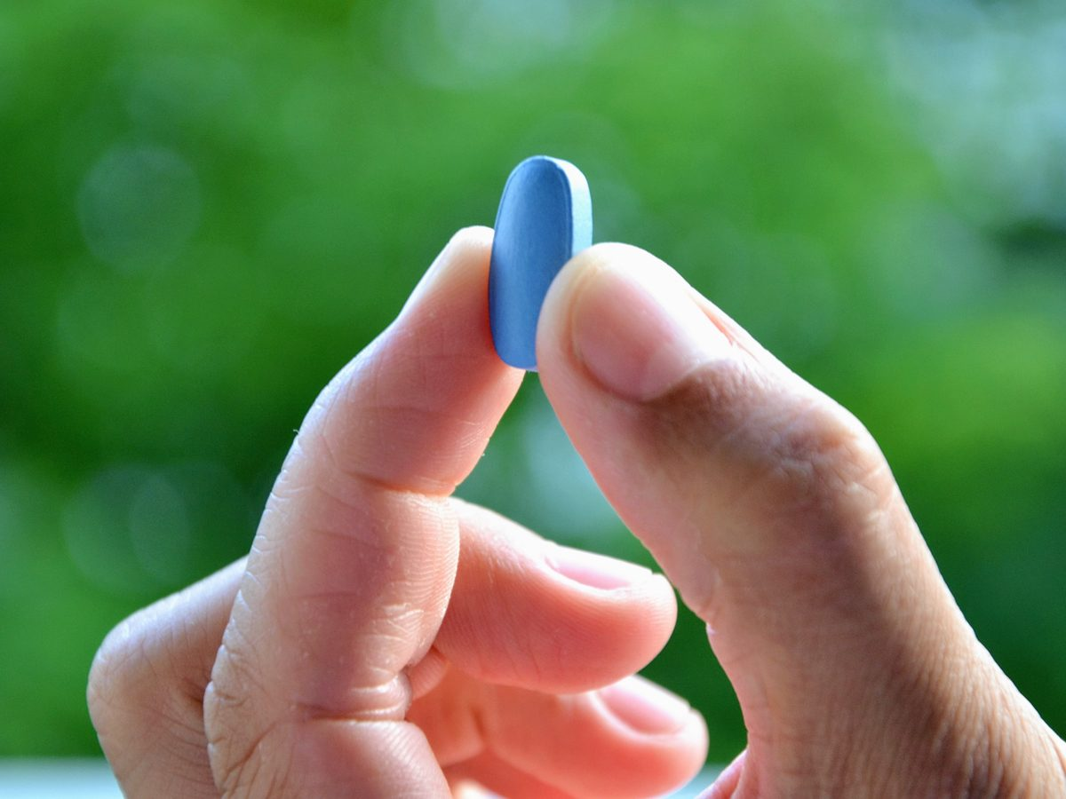Hands holding a blue pill