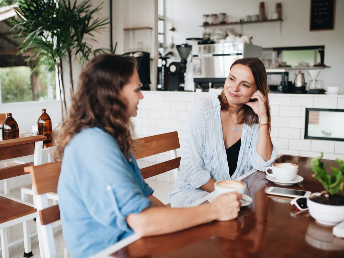 Two attractive female friends laughing in cafe