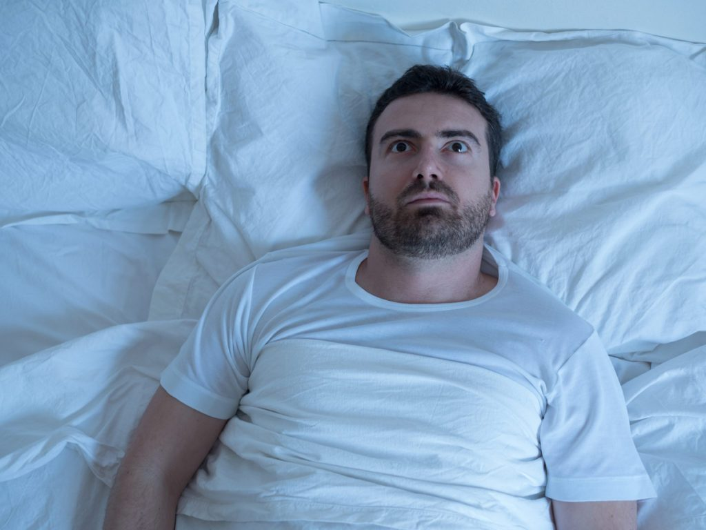Man lying in bed staring at ceiling