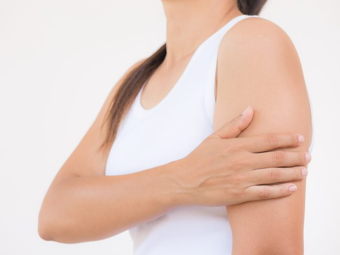 heart attack symptoms - Woman clutching left arm