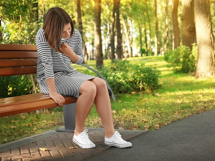 Woman on bench outside holding chest