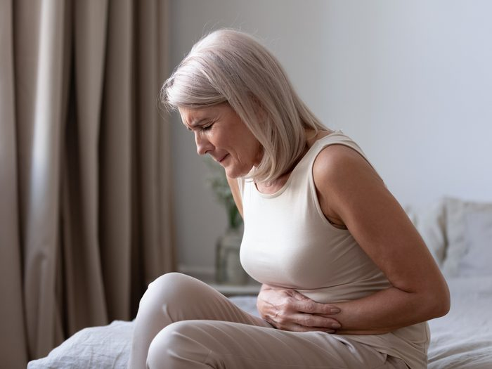 heart attack symptoms - Woman holding stomach in pain