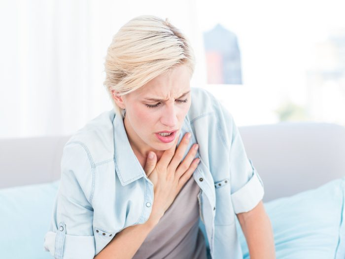 Woman with hand to chest short of breath