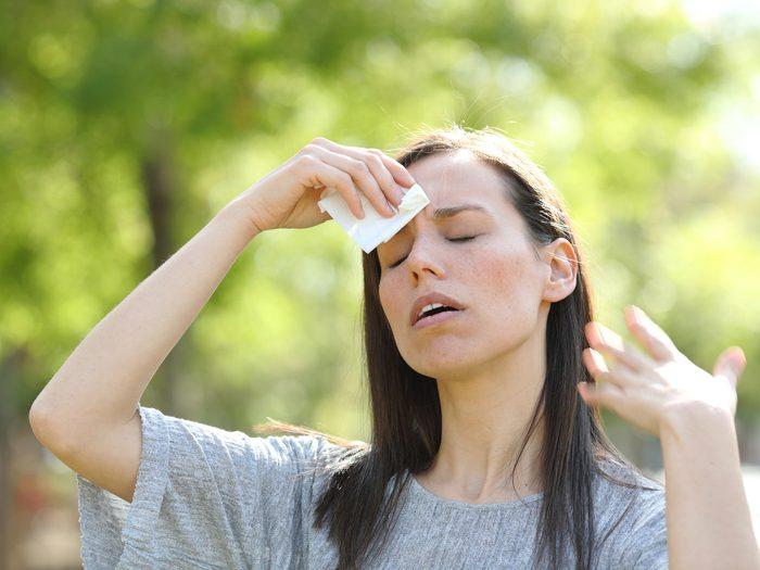 Heart attack symptoms - Woman dabbing sweaty forehead