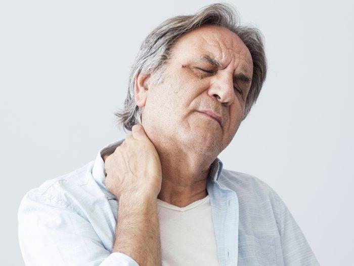 heart attack symptoms - Senior man holding neck