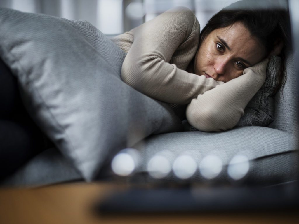 Woman lying in bed facing camera appearing sad