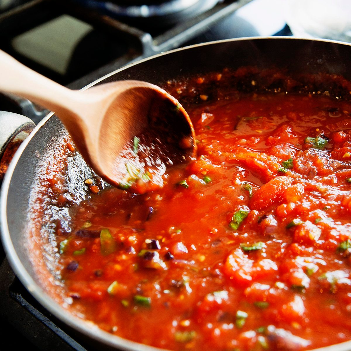Vilnius, Lithuania - June 17, 2011: preparing of a homemade tomato sauce in a frying pan from fresh tomatoes.