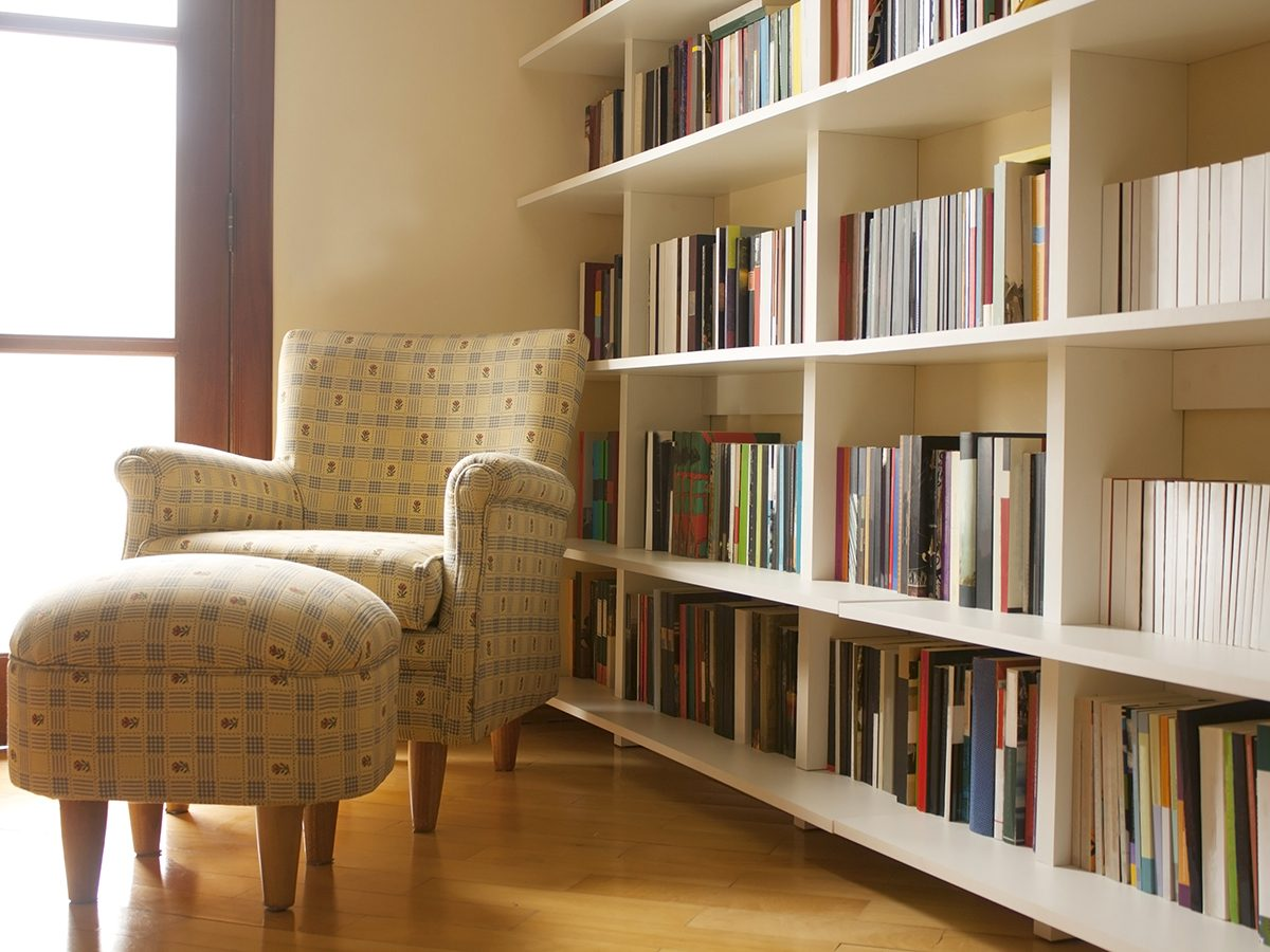 Home library with arm chair. Clean and modern decoration. Light coming from the window.