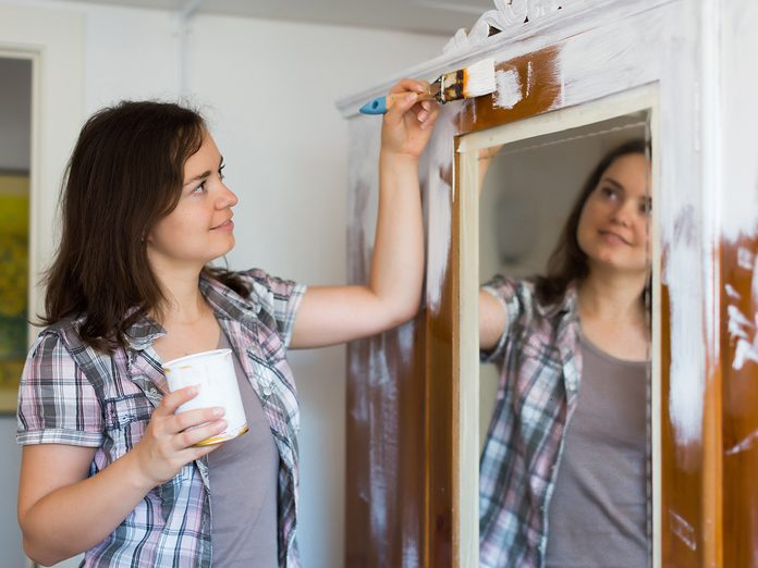 Young woman paints closet and makes repairs in the apartment ..
