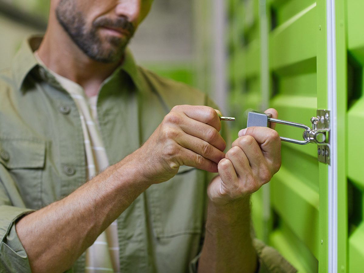 Close up of handsome man opening padlock on door of self storage unit , copy space