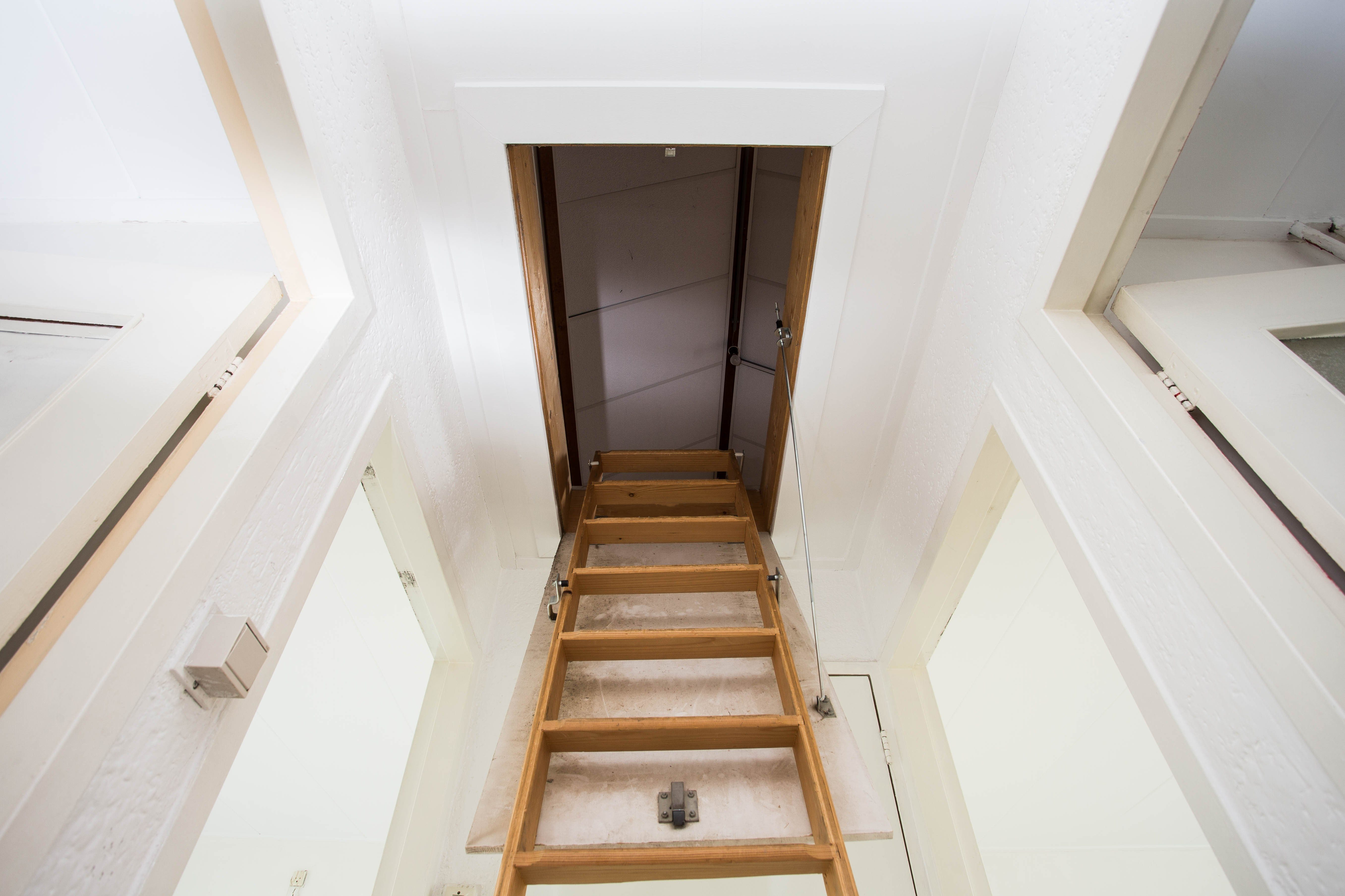 Wooden staircase to the attic in a modern house empty