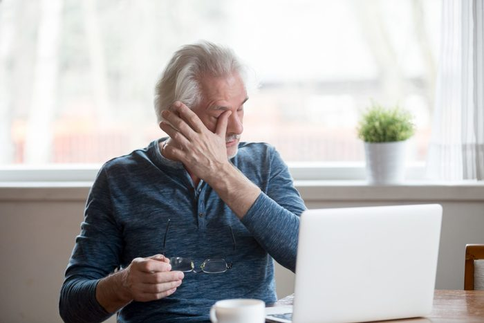 Signs you need new glasses - senior middle aged male feels eye strain problem or blurry vision working on laptop at home