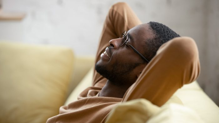 Signs you need new glasses - man in glasses sit relax on cozy couch lean hands over head taking nap in living room,