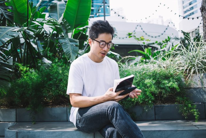 Signs you need new glasses - male student in glasses sitting on bench in park with crossed legs and looking at book and smartphone in hands