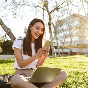 Photo of happy woman sitting on grass outdoors using laptop computer and mobile phone.