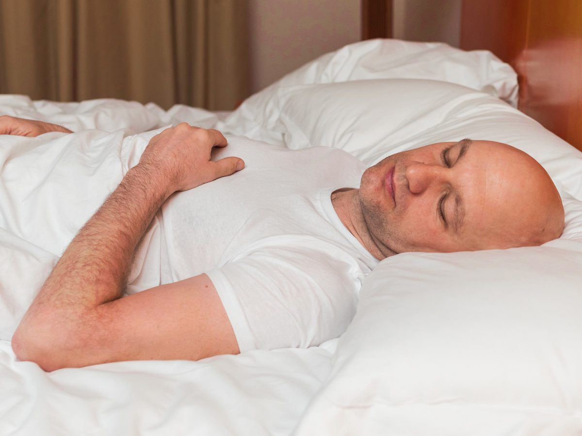 Bald Caucasian man sleeping in bed