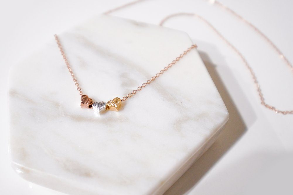 three love pendant necklace on white hexagon marble