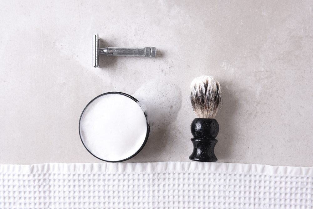 Shaving Still Life: Safety razor with towel, brush and soap on a gray tile surface.