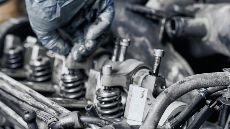 Gloved hand fixing a car engine