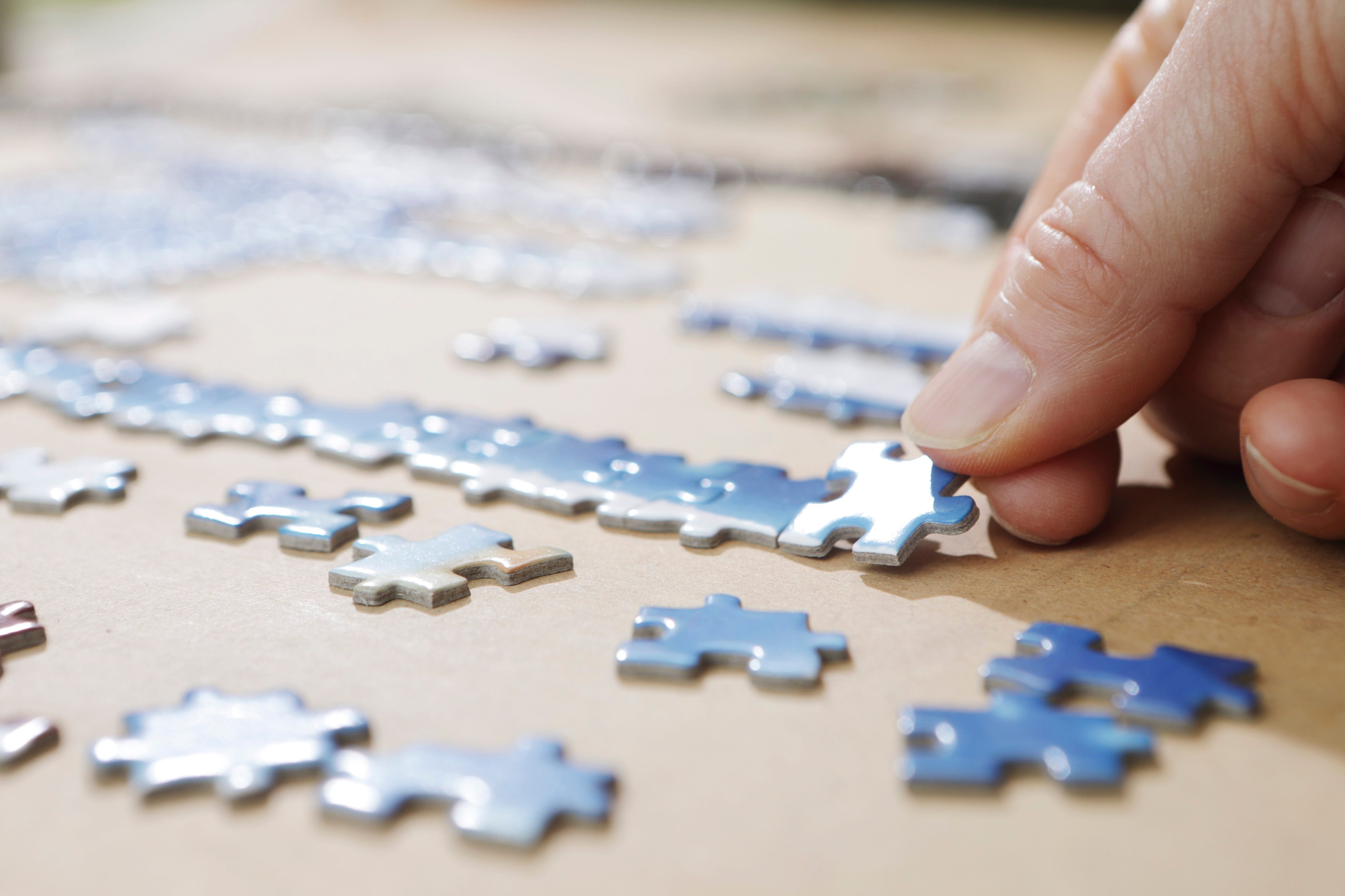 Hand placing puzzle pieces on a board