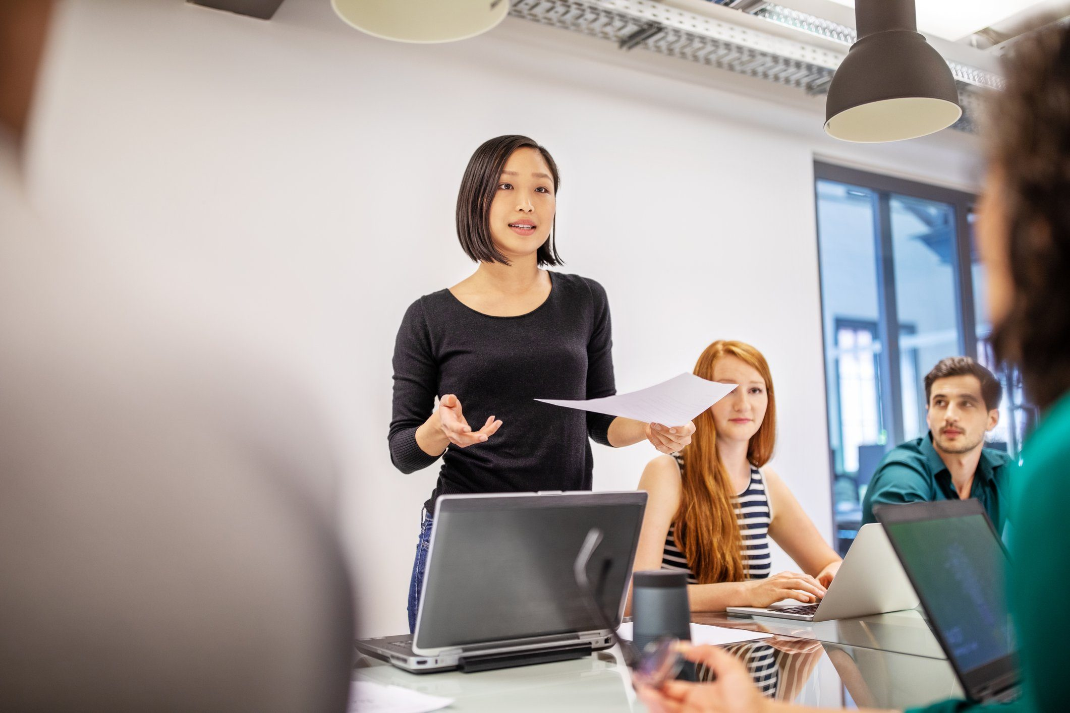 Confident female professional discussing with colleagues