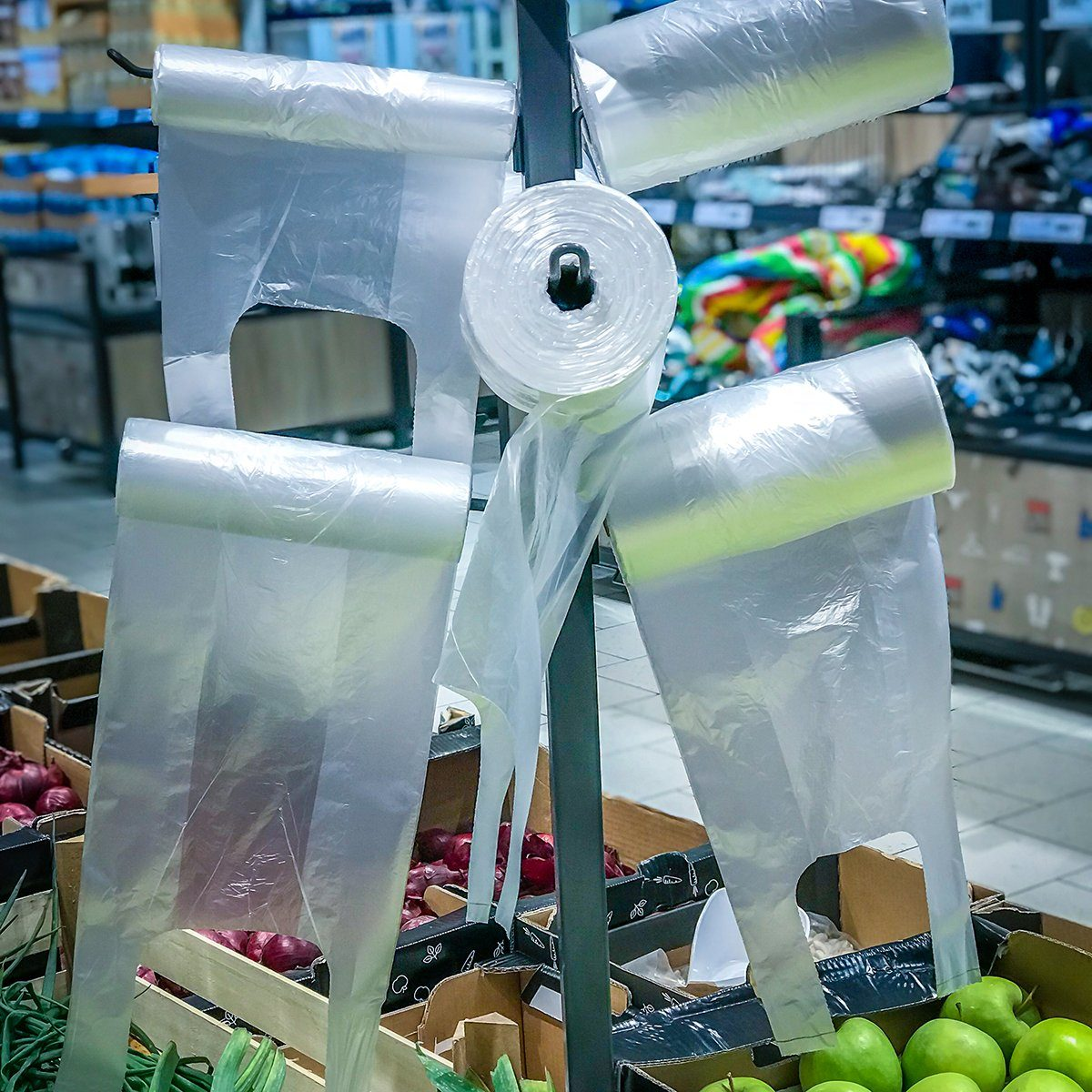 Plastic cellophane bags hanging on the stand in the supermarket fruits - vegetables department.