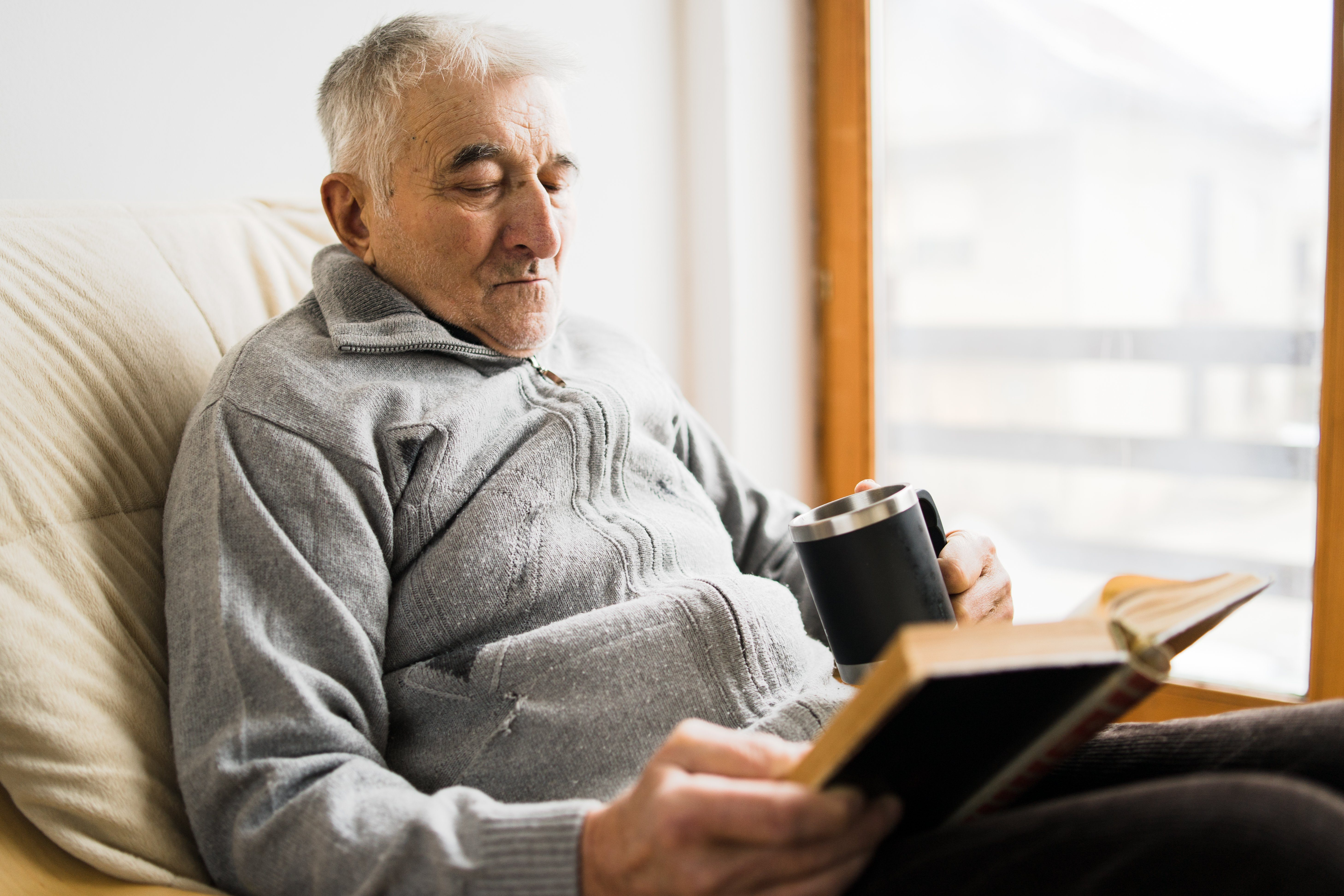 Senior man sitting and Reading a book at the retirement nursing home with cup of tea in hand