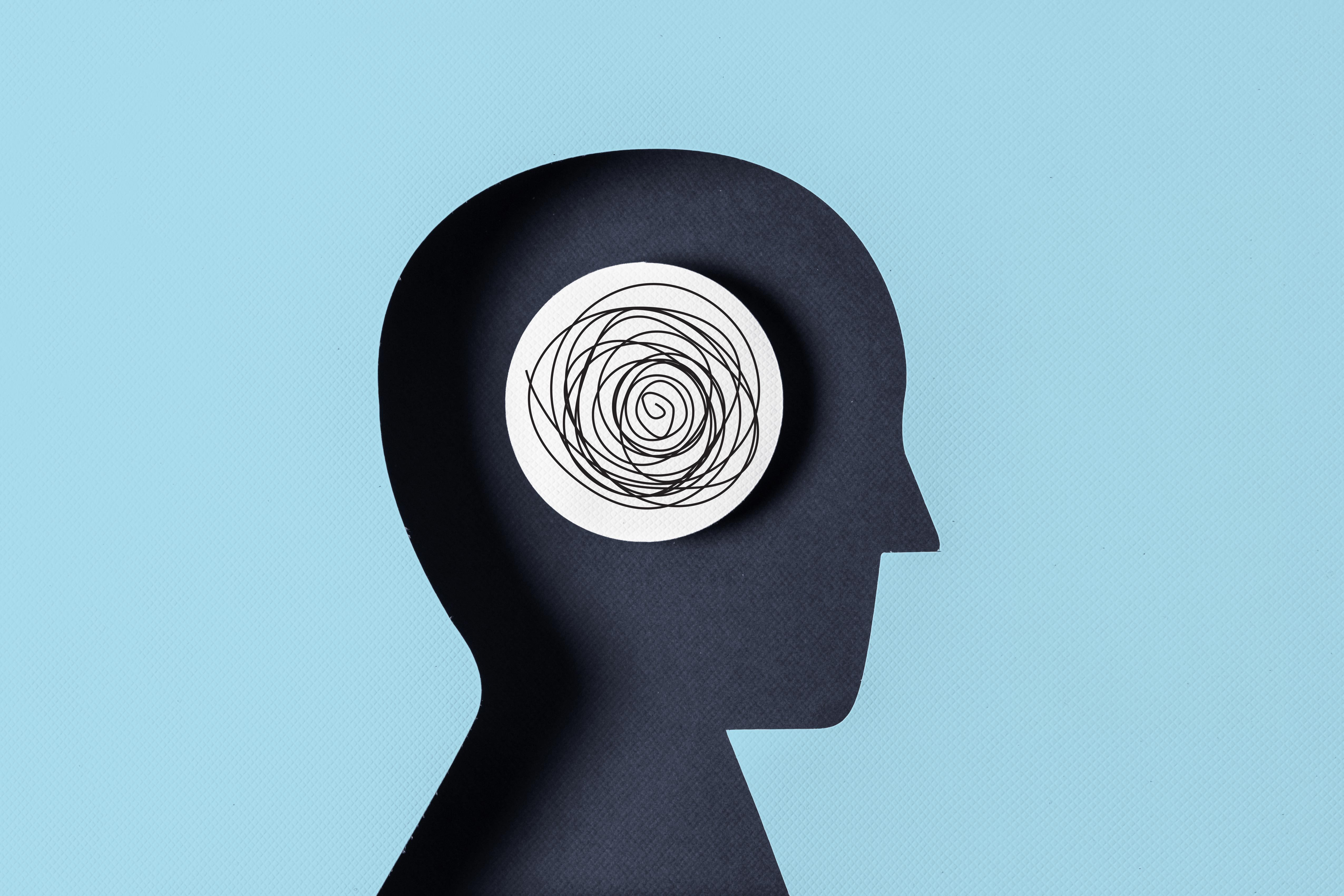 paper silhouette of a head. scibbled circles in the brain.