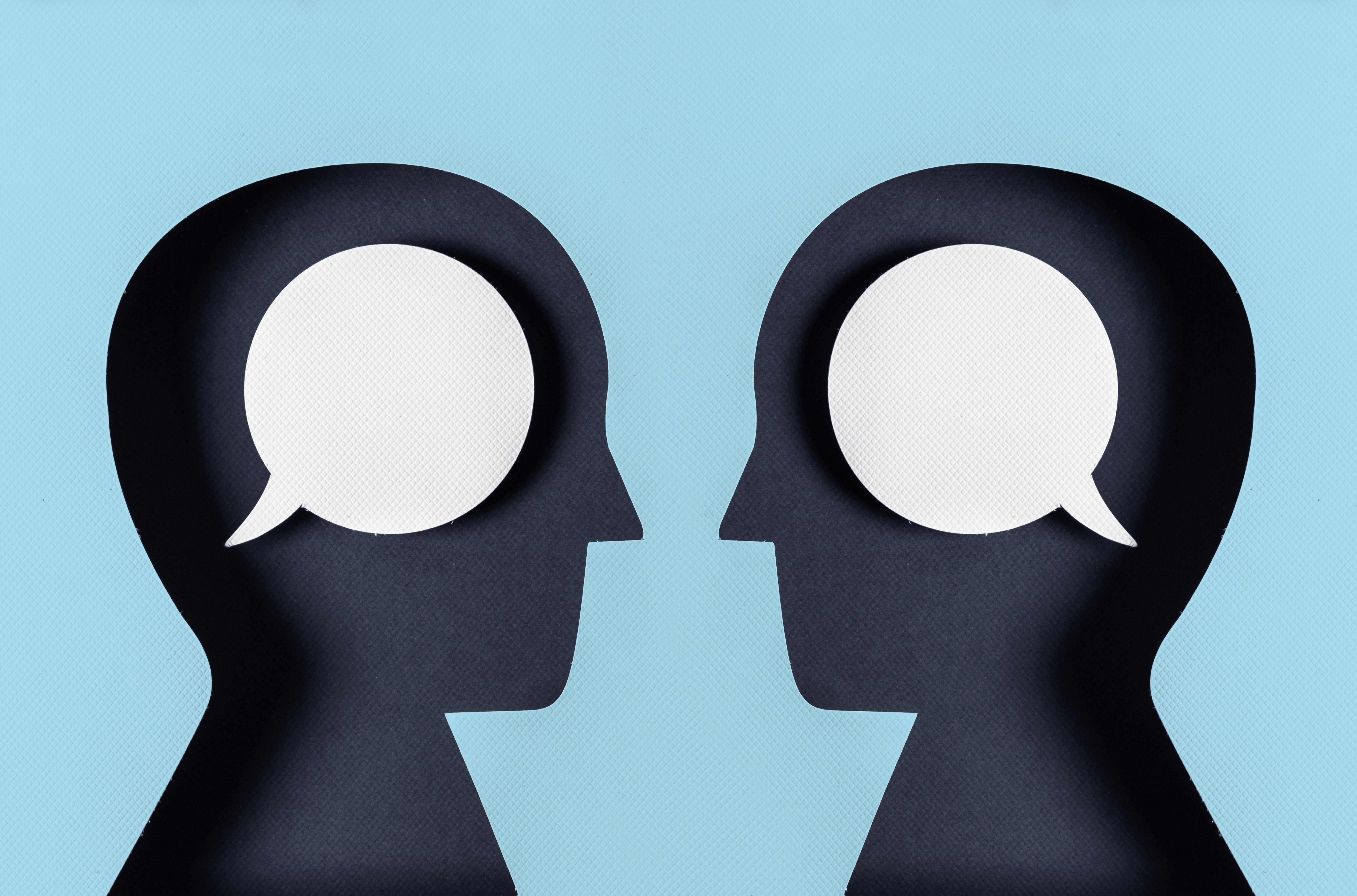 two head silhouettes. speech bubbles in the brains.