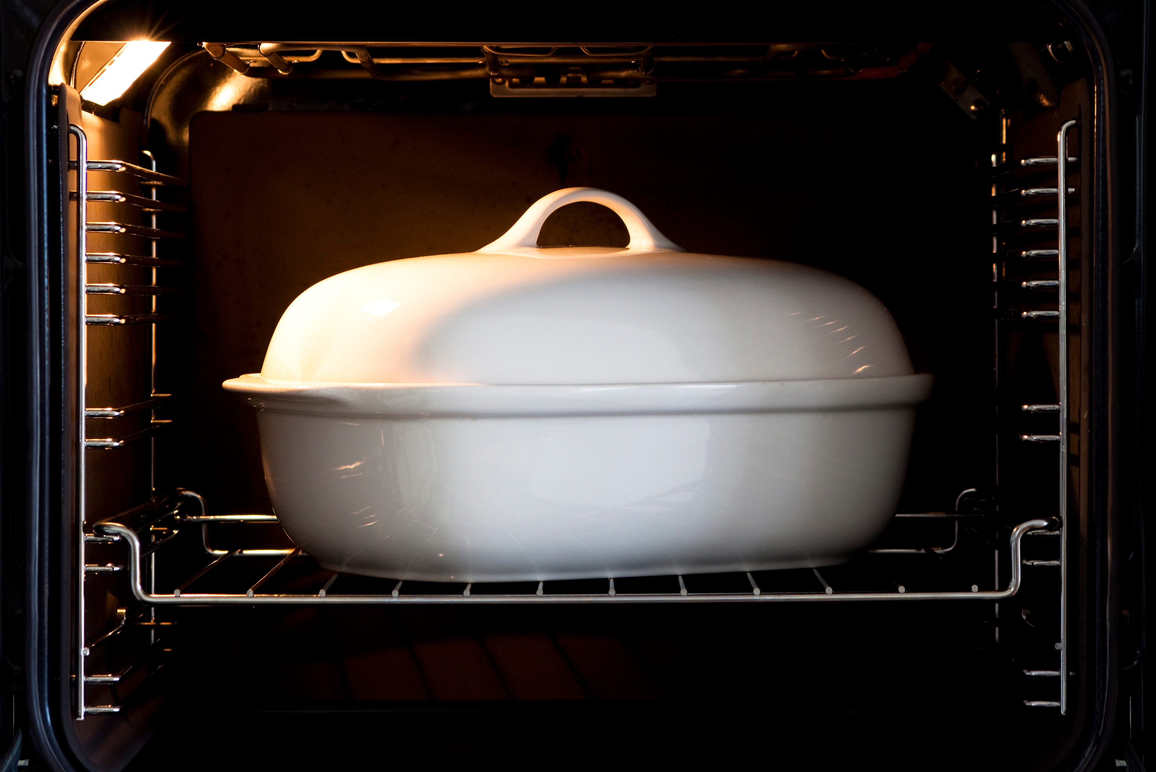 White porcelain baking dish with lid in open owen