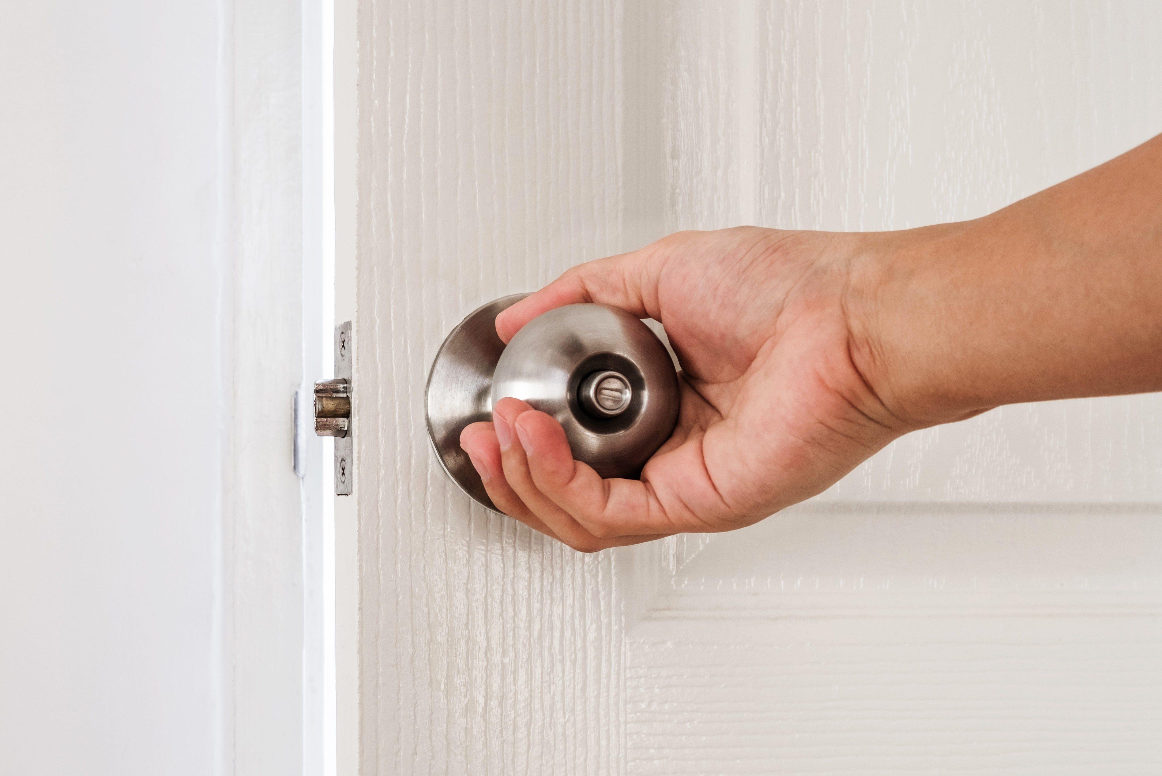Hand holding door knob, white door and wall