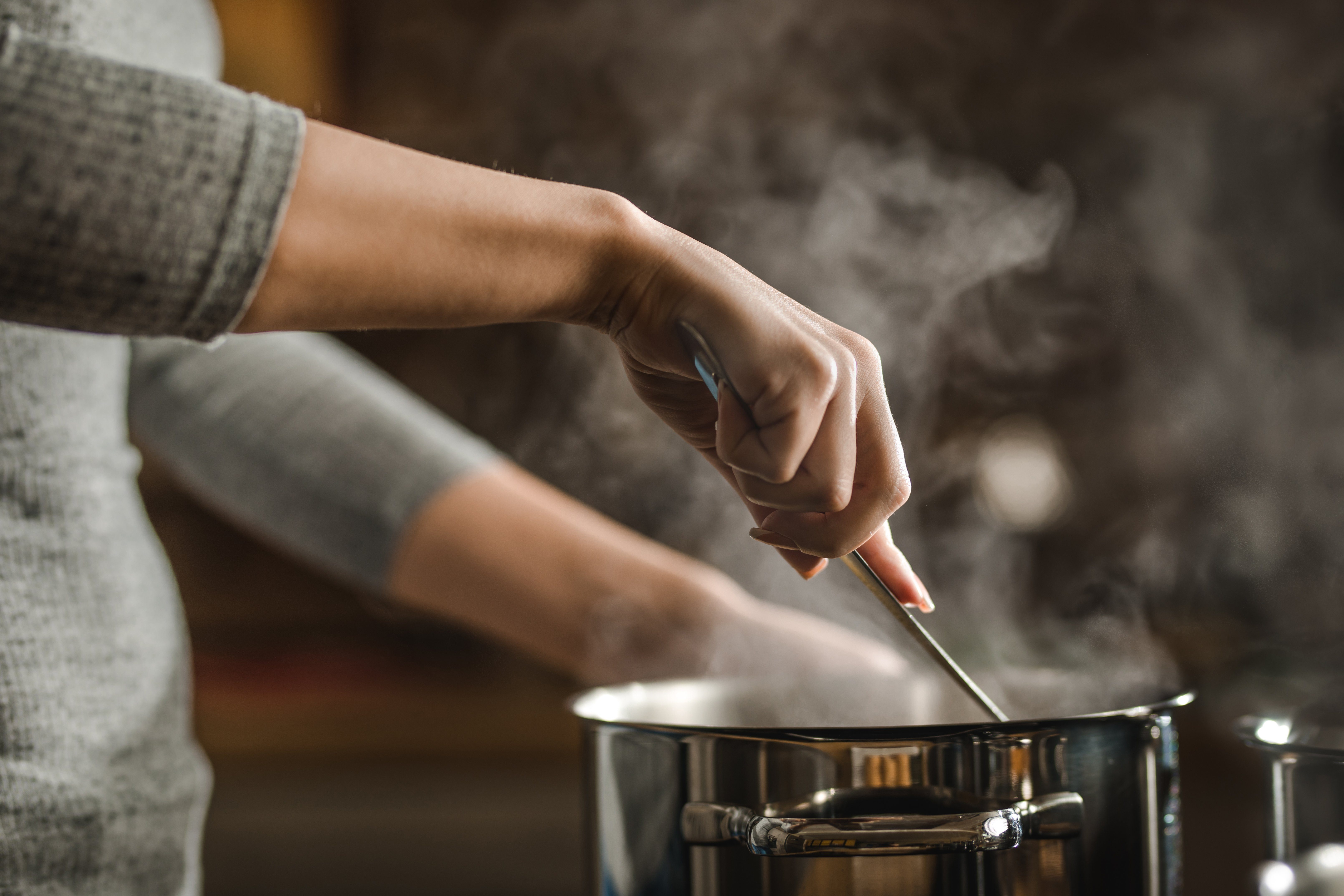 Unrecognizable woman stirring soup in a saucepan while making lunch.