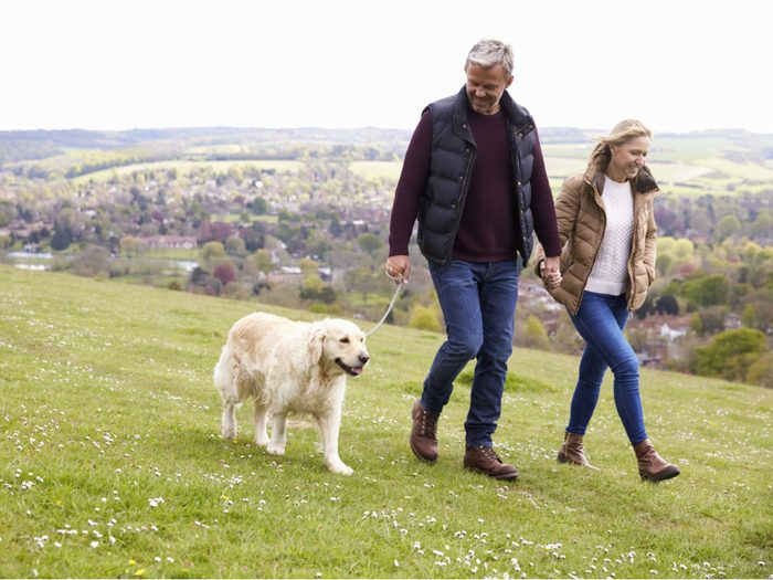 Middle-aged couple walking on a hillside with their dog