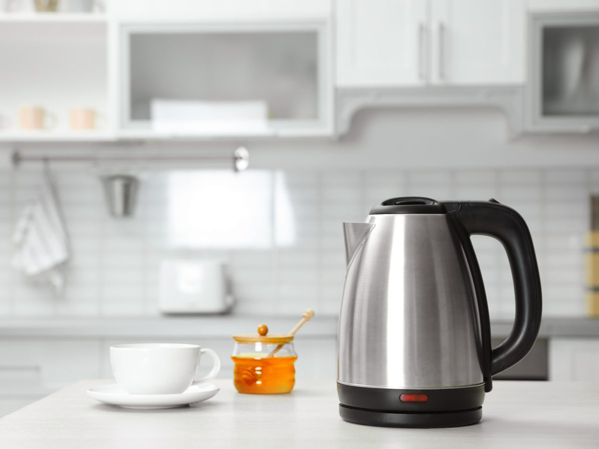 Tea kettle, honey and tea cup in kitchen concept