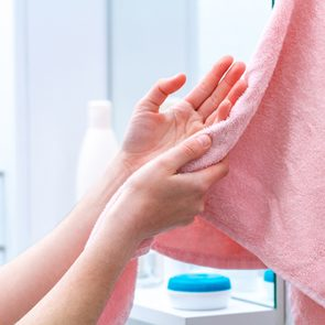 Person using towel for wiping hands dry after washing in bathroom at home. Hygiene and hand care